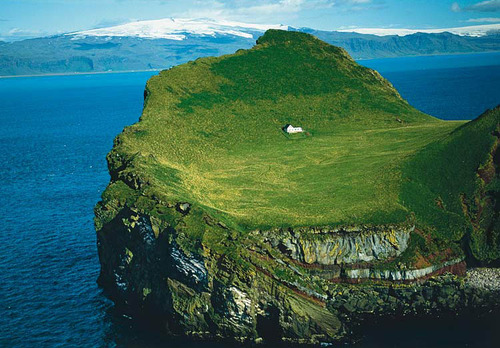 A picture of an awesome green island with cliffs and mountains in the background.